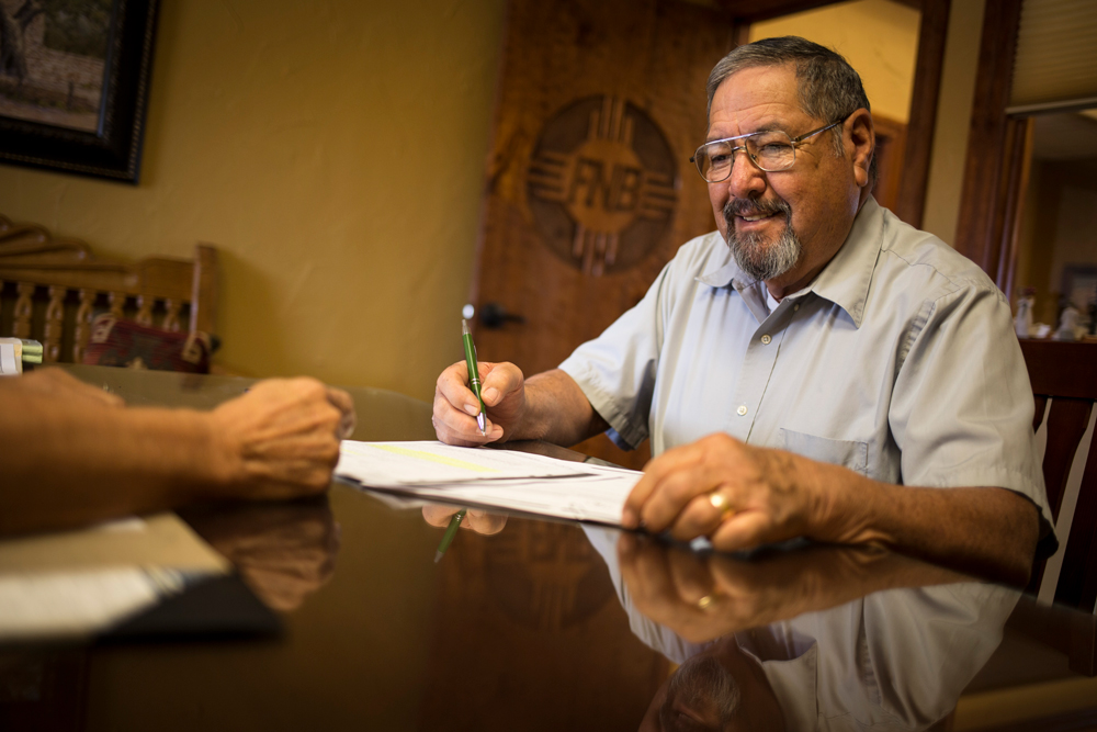man signing papers at FNB New Mexico